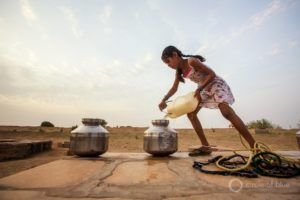 A girl fills jars with water in Rajasthan, India. Photo © J. Carl Ganter / Circle of Blue